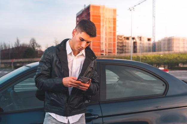 Молодой кавказский человек с помощью смартфона со спортивным автомобилем позади