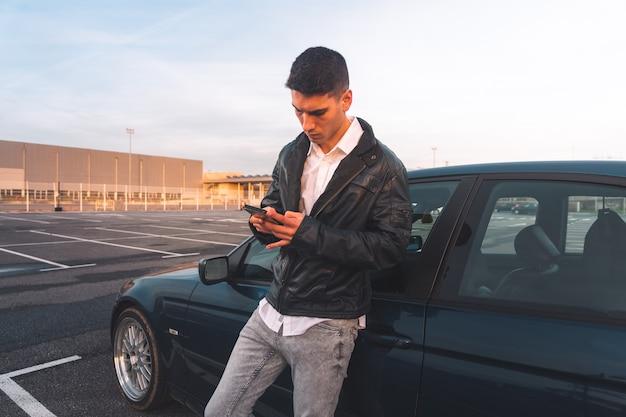 後ろにスポーツカーとスマートフォンを使用して若い白人男性