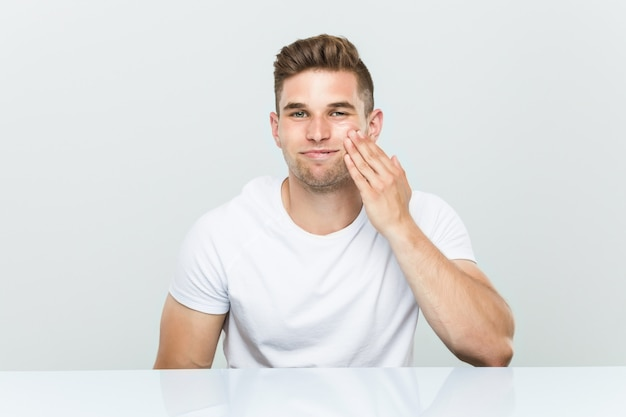 Young caucasian man using facial moisturizer