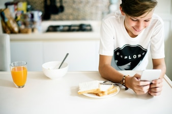 Young caucasian man using mobile phone in kitchen
