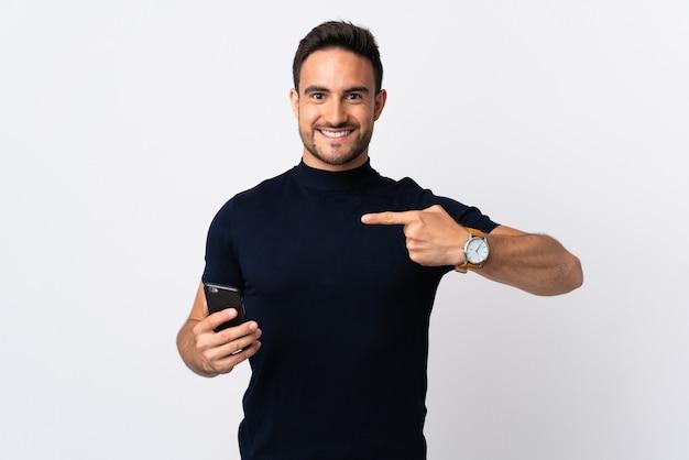 흰색 배경에 고립 된 휴대 전화를 사용 하 고 그것을 가리키는 젊은 백인 남자