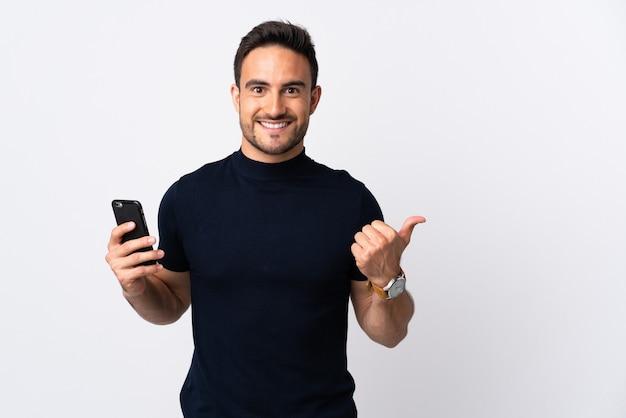 製品を提示する側を指している白で隔離の携帯電話を使用して若い白人男性