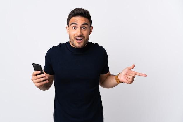 白い壁に隔離された携帯電話を使用して若い白人男性が驚いて、人差し指を横に向ける