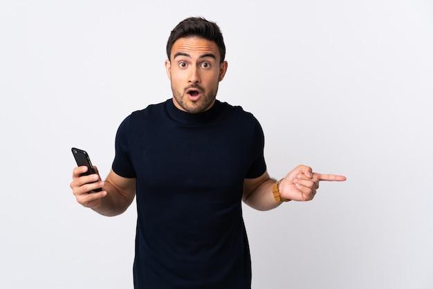 Молодой кавказский человек с помощью мобильного телефона, изолированного на белой стене, удивился и указал сторону