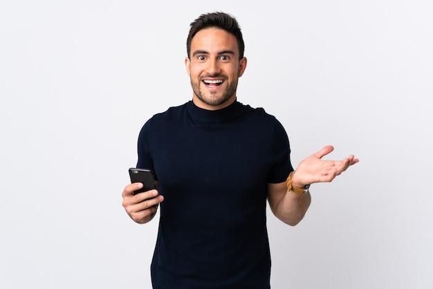 Молодой кавказский человек разговаривает по мобильному телефону, изолирован на белой стене с шокированным выражением лица
