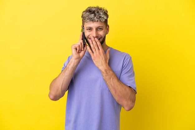 노란색 배경에 격리된 휴대전화를 사용하는 백인 청년은 행복하고 손으로 입을 가리고 웃고 있다