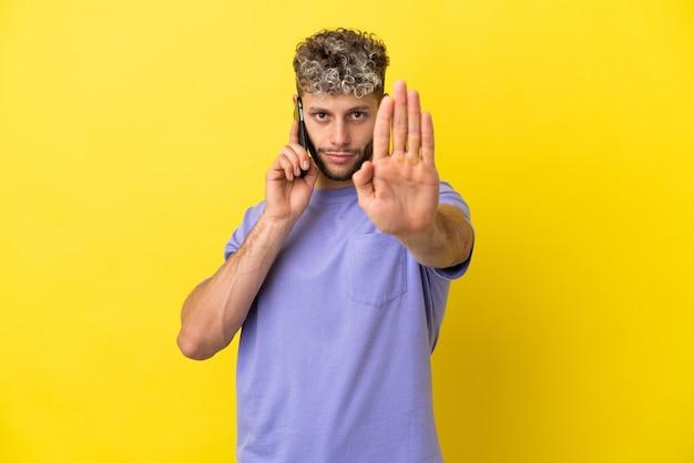 정지 제스처를 만드는 노란색 배경에 고립 된 휴대 전화를 사용 하는 젊은 백인 남자