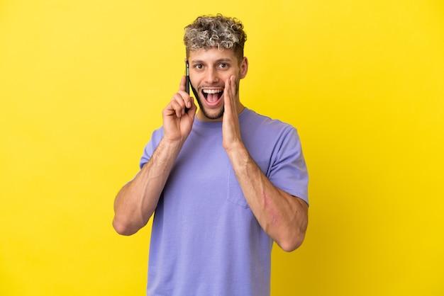 놀람과 놀란 표정으로 노란색 배경에 고립 된 휴대 전화를 사용하는 젊은 백인 남자
