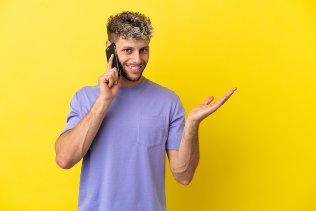 Young caucasian man using mobile phone isolated on yellow background extending hands to the side for inviting to come