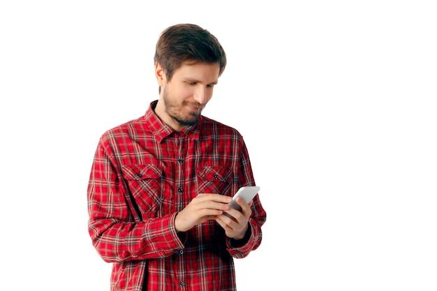 Giovane uomo caucasico che utilizza smartphone mobile isolato sulla parete bianca dello studio. concetto di moderne tecnologie, gadget, tecnologia, emozioni, pubblicità. copyspace. messaggio di battitura. navigazione in linea.