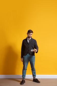 노란색 벽 위에 절연 스마트 폰 전신 길이 초상화를 사용하는 젊은 백인 남자 무료 사진