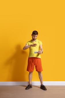 Молодой кавказский человек с помощью смартфона в полный рост портрет изолирован над желтой стеной