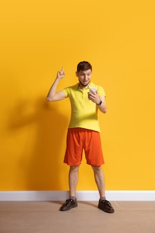 黄色の壁に分離されたスマートフォンの全身の長さの肖像画を使用して若い白人男性