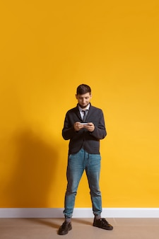 Young caucasian man using smartphone full body length portrait isolated over yellow wall
