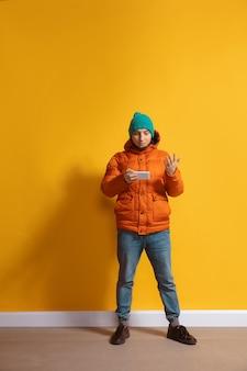 Giovane uomo caucasico che utilizza il ritratto completo di lunghezza del corpo dello smartphone isolato sopra la parete gialla