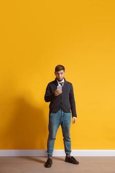 노란색 위에 스마트폰 전신 길이 초상화를 사용하는 젊은 백인 남자