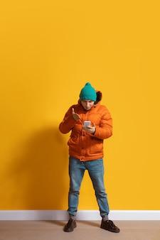Giovane uomo caucasico utilizza lo smartphone, servi la gleba, chiacchierando, scommettendo.