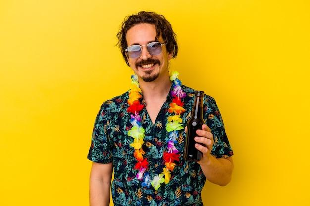 행복 하 고 웃 고 쾌활 한 노란색 벽에 고립 된 맥주를 들고 하와이 목걸이 입고 젊은 백인 남자.