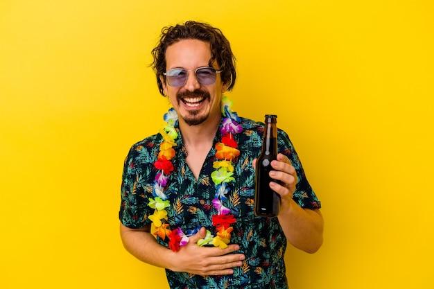 노란색 벽 웃음과 재미에 고립 된 맥주를 들고 하와이 목걸이 입고 젊은 백인 남자.