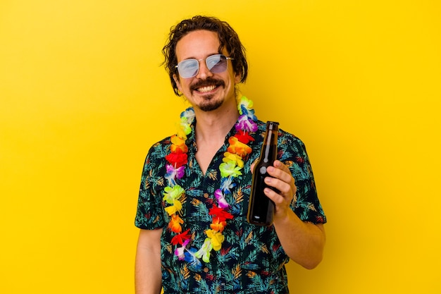 노란색 벽에 고립 된 맥주를 들고 하와이 목걸이를 입고 젊은 백인 남자는 옆으로 웃고, 밝고 쾌적합니다.