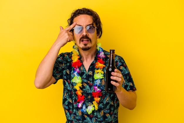 집게 손가락으로 실망 제스처를 보여주는 노란색 벽에 고립 된 맥주를 들고 하와이 목걸이 입고 젊은 백인 남자.