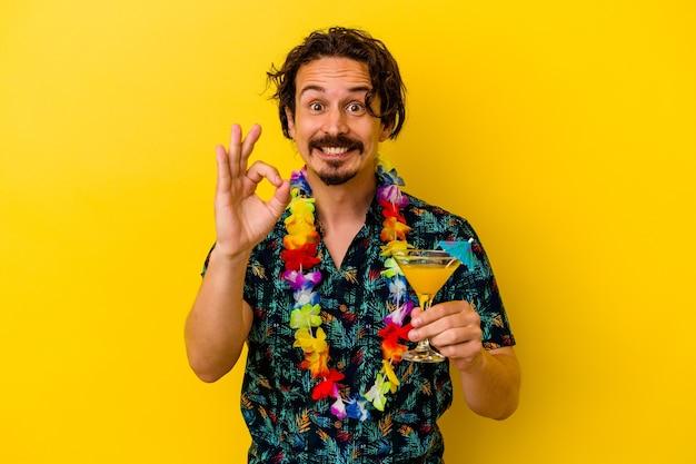 노란색 벽 명랑 하 고 확신 보여주는 확인 제스처에 고립 된 칵테일을 들고 하와이 목걸이 입고 젊은 백인 남자.