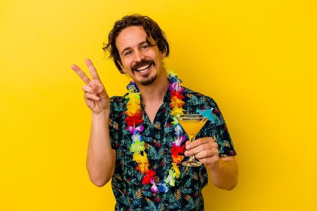 손가락으로 평화의 상징을 보여주는 즐겁고 평온한 노란색 벽에 고립 된 칵테일을 들고 하와이 목걸이를 입고 젊은 백인 남자.