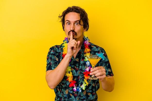 비밀을 유지하거나 침묵을 요구하는 노란색 벽에 고립 된 칵테일을 들고 하와이 목걸이를 착용하는 젊은 백인 남자.