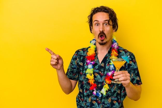 측면을 가리키는 노란색 벽에 고립 된 칵테일을 들고 하와이 목걸이를 입고 젊은 백인 남자