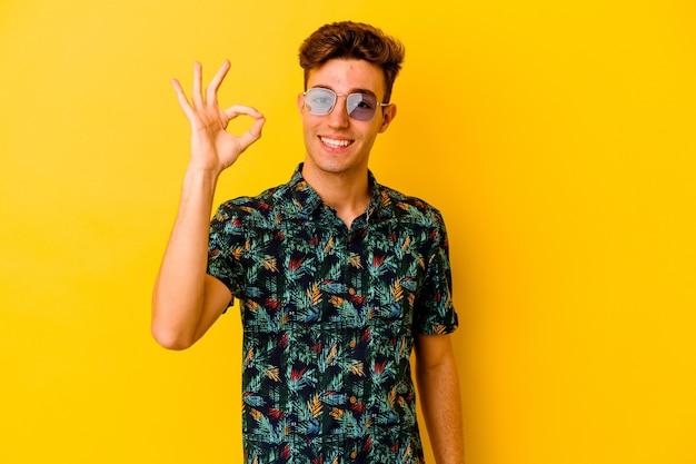 노란색 벽 명랑 하 고 확신 보여주는 확인 제스처에 고립 된 하와이안 셔츠를 입고 젊은 백인 남자.