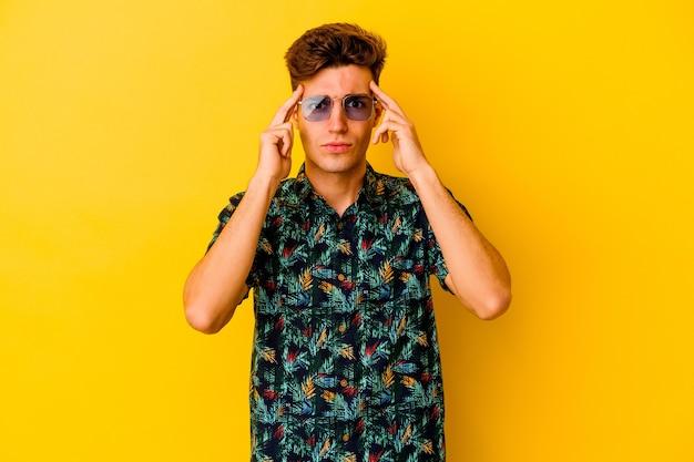 노란색 벽에 고립 된 하와이안 셔츠를 입고 젊은 백인 남자는 머리를 가리키는 집게 손가락을 유지하는 작업에 초점을 맞춘.