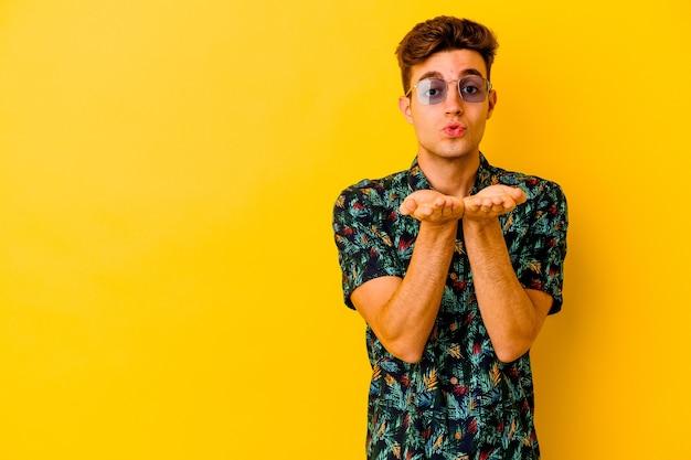 노란색 벽에 입술을 접고 손바닥을 잡고 공기 키스를 보내 절연 하와이안 셔츠를 입고 젊은 백인 남자.