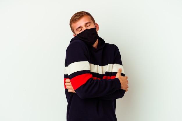 白い壁に隔離されたウイルスのマスクを身に着けている若い白人男性は、のんびりと幸せに笑って抱擁します。