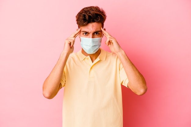 분홍색 벽에 고립 된 코로나 바이러스에 대한 보호를 착용하는 젊은 백인 남자는 작업에 집중하고 집게 손가락이 머리를 가리키는 유지