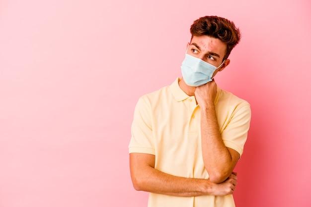 Молодой кавказский мужчина, одетый в защиту от коронавируса, изолированный на розовой стене, чувствует себя грустным и задумчивым, глядя на пространство для копирования.