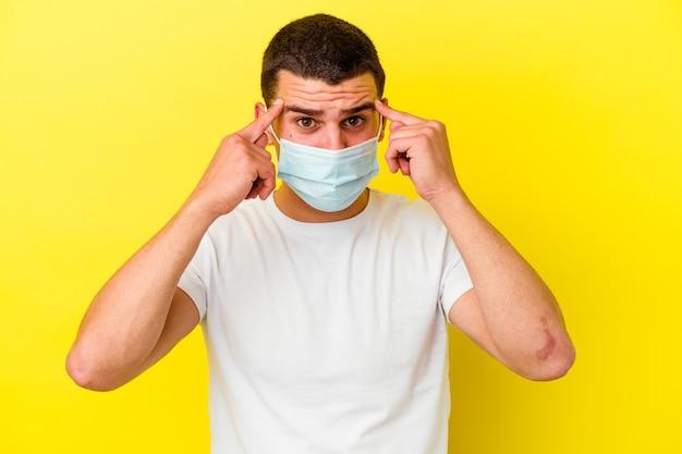 Молодой кавказский мужчина в защитном чехле от коронавируса на желтом фоне сосредоточился на задаче, держа указательные пальцы указывая головой.