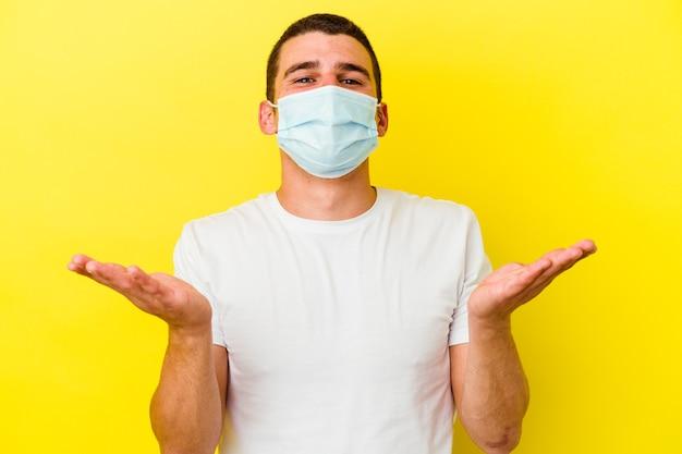 歓迎の表現を示す黄色で分離されたコロナウイルスの保護を身に着けている若い白人男性。