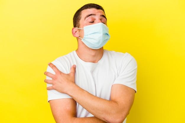 黄色い壁の抱擁で分離されたコロナウイルスの保護を身に着けている若い白人男性は、のんきと幸せに笑っています。