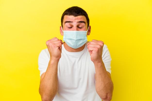 Молодой кавказский мужчина с защитой от коронавируса изолирован на желтой стене, поднимая кулак, чувствуя себя счастливым и успешным