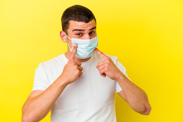 分離されたコロナウイルスの保護を身に着けている若い白人男性