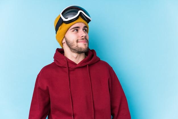 目標と目的を達成することを夢見て孤立したスキー服を着ている若い白人男性