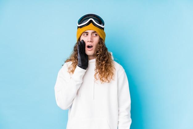孤立したスキー服を着ている若い白人男性は、秘密のホットブレーキのニュースを言って脇を見ています