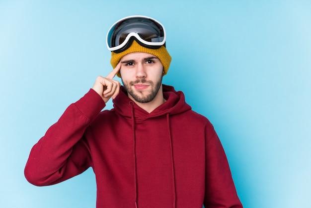 スキー服を着た若い白人男性は、指で寺院を指して、考え、仕事に集中しました。