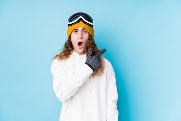 横を指して孤立したスキーウェアを着ている若い白人男性