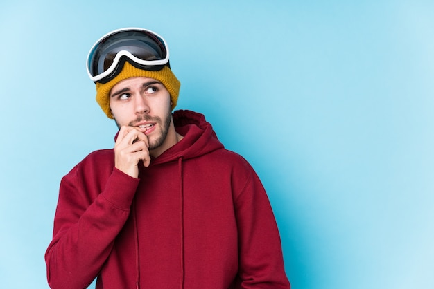 スキー服を着た若い白人男性は、コピースペースを見ている何かについて考えてリラックスしました。