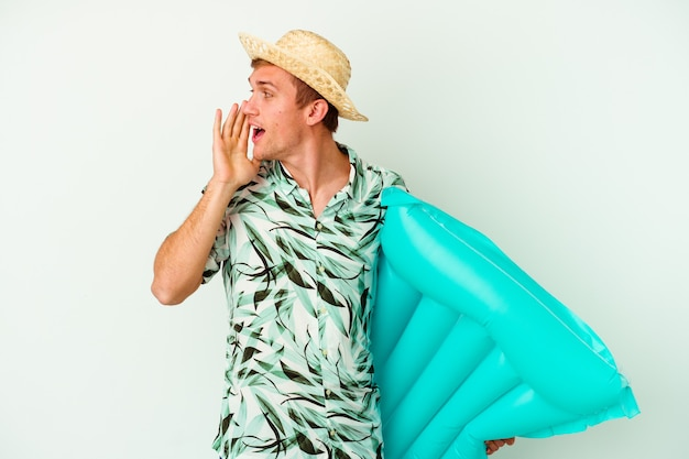 여름 옷을 입고 흰색 배경에 고립 된 공기 매트리스를 들고 젊은 백인 남자가 외치고 열린 입 근처에 손바닥을 들고.