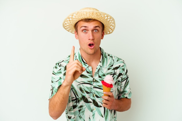 젊은 백인 남자 여름 옷을 입고 아이디어, 영감 개념을 갖는 흰색 배경에 고립 된 아이스크림을 들고.