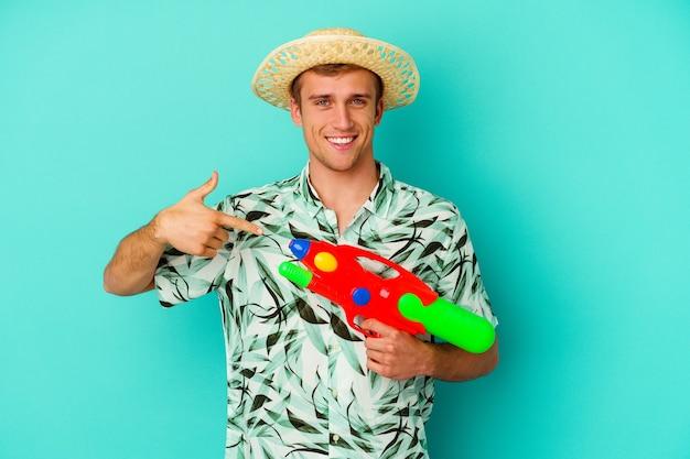 젊은 백인 남자 여름 옷을 입고 셔츠 복사 공간을 손으로 가리키는 흰색 배경 사람에 고립 물 총을 들고, 자랑스럽고 자신감