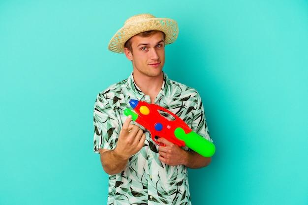 Молодой кавказский мужчина в летней одежде и держит водяной пистолет, изолированный на белой стене, указывая пальцем на вас, как будто приглашая подойти ближе.