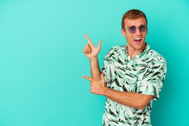 젊은 백인 남자는 복사 공간을 집게 손가락으로 가리키는 파란색 배경에 고립 된 여름 옷을 입고 흥분과 욕망을 표현합니다.